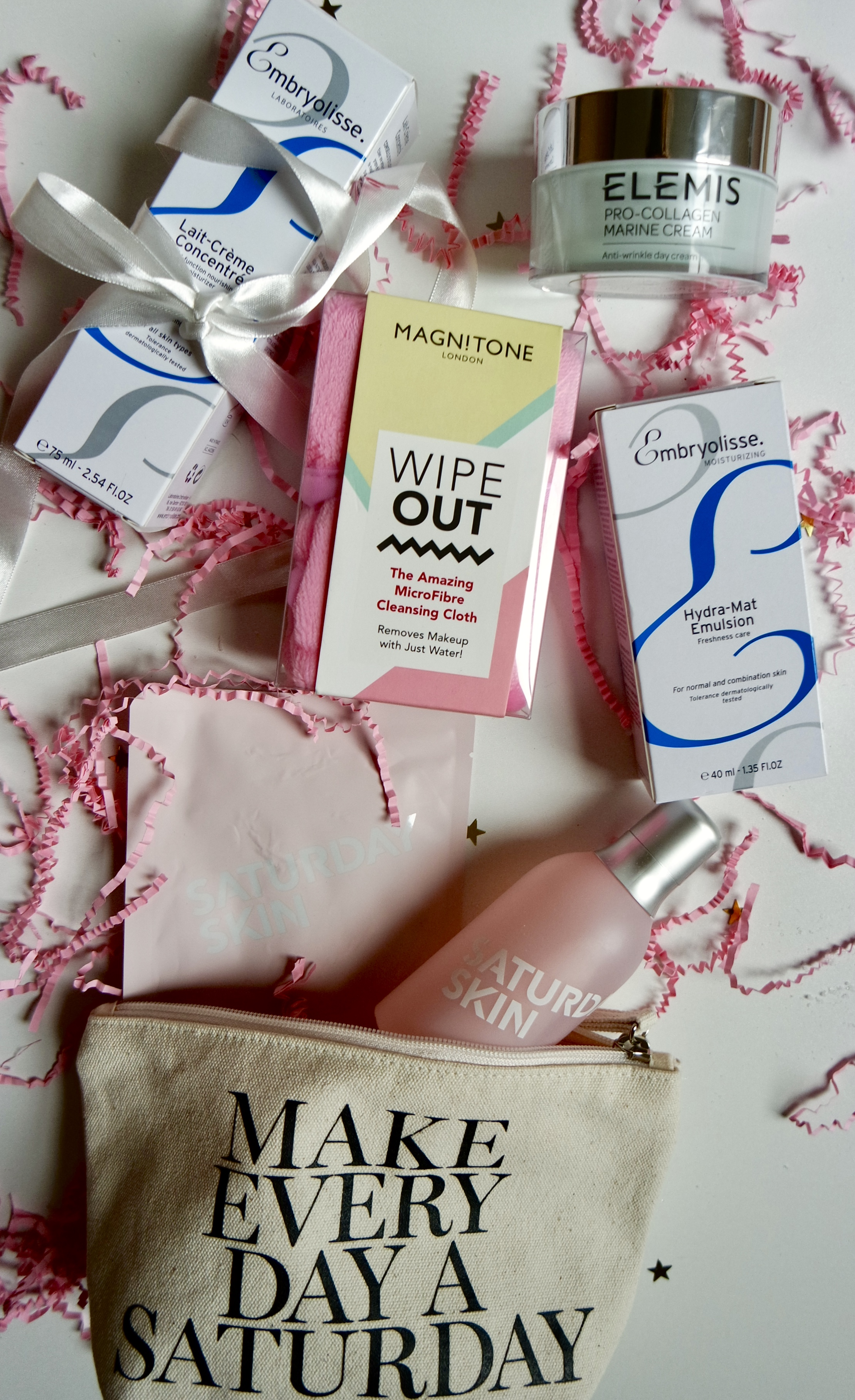 Beauty Christmas Gift Guide Flatlay of skincare products on white background with pink confetti around - Embryolisse, Elemis, Magnitone, Saturday skin products