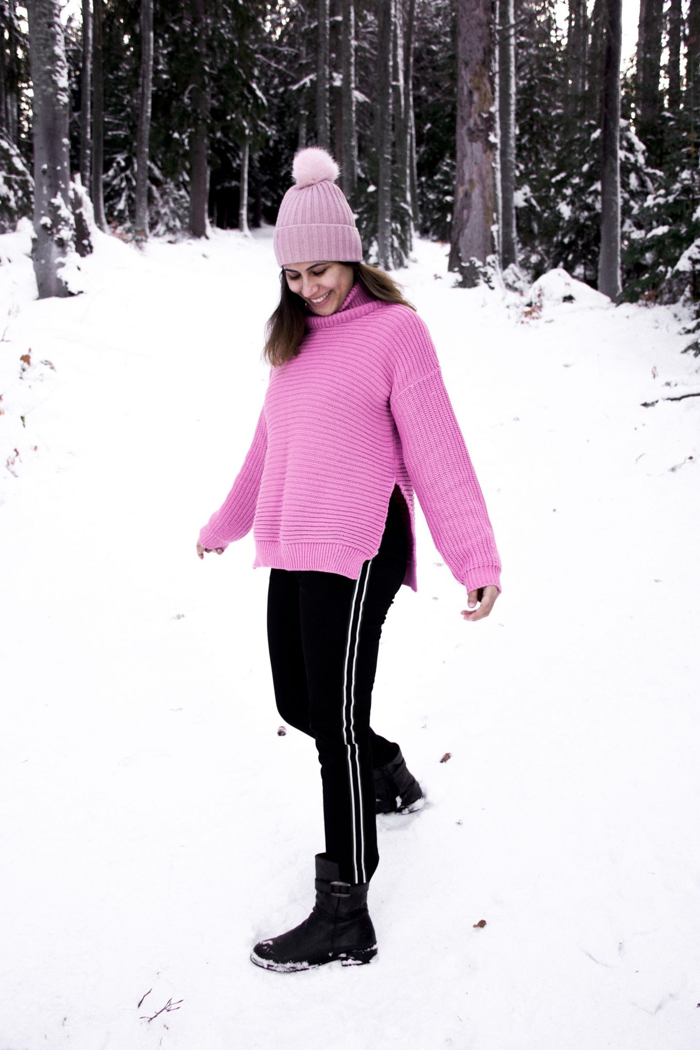 Girl in mountains walking down snowy slope wearing pink jumper and pink hat