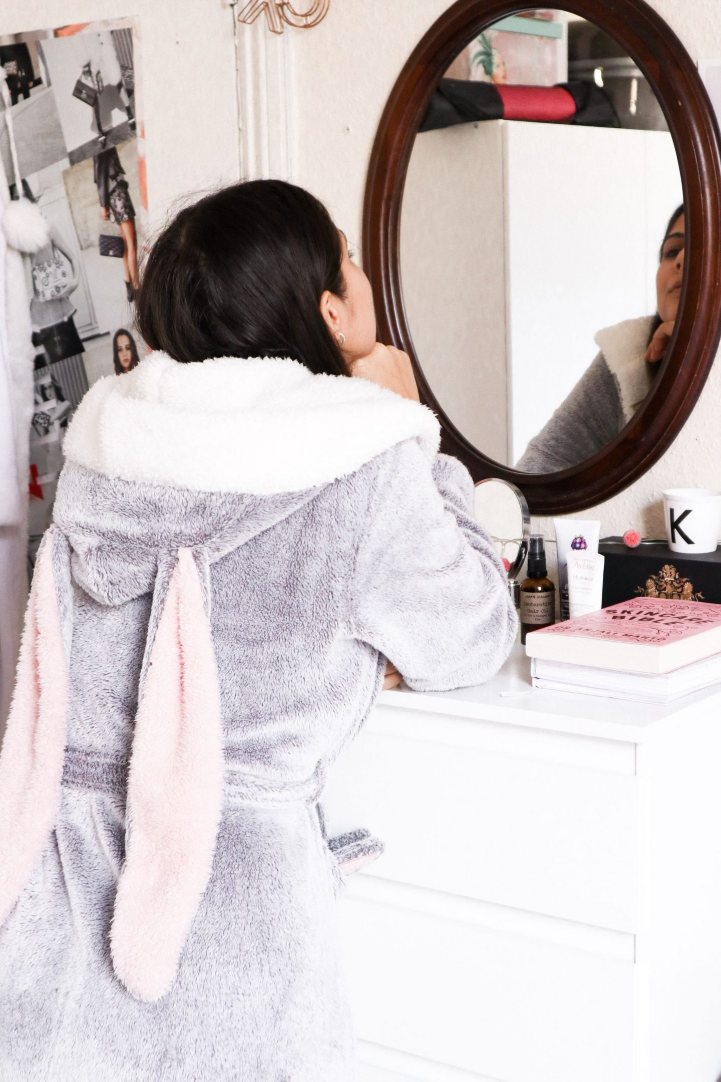 Girl in Bunny hunkemoller bathrobe looking at herself in mirror on the wall
