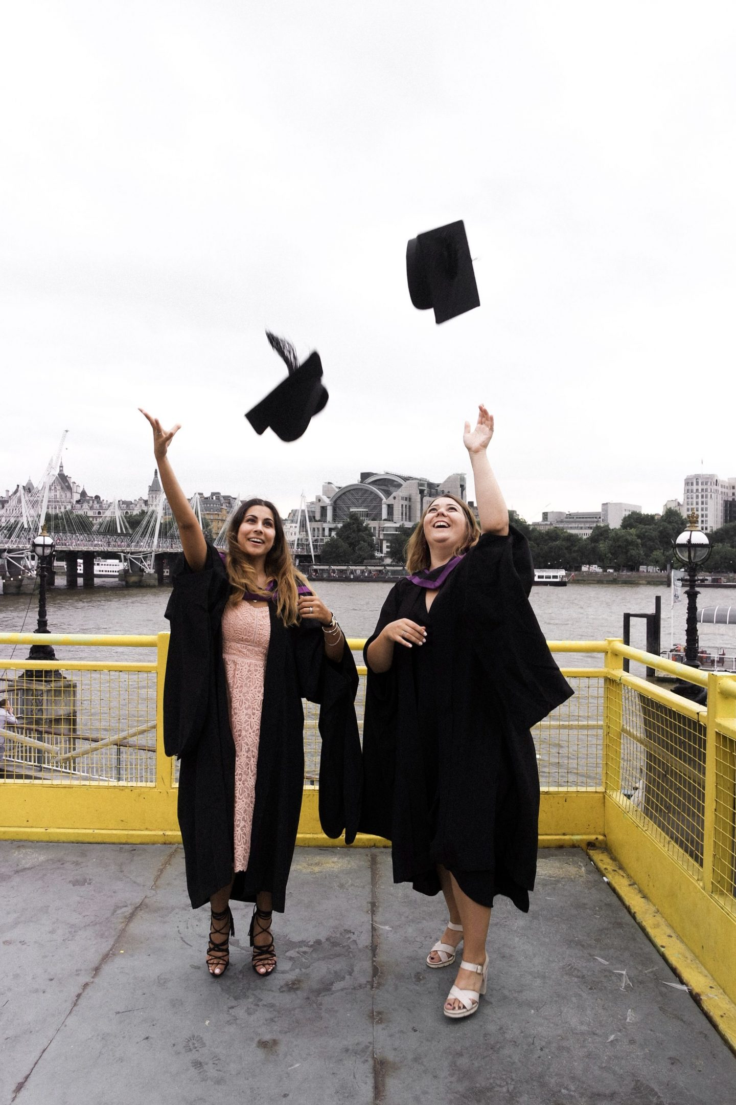 Two girls throwing graduation caps London Southbank