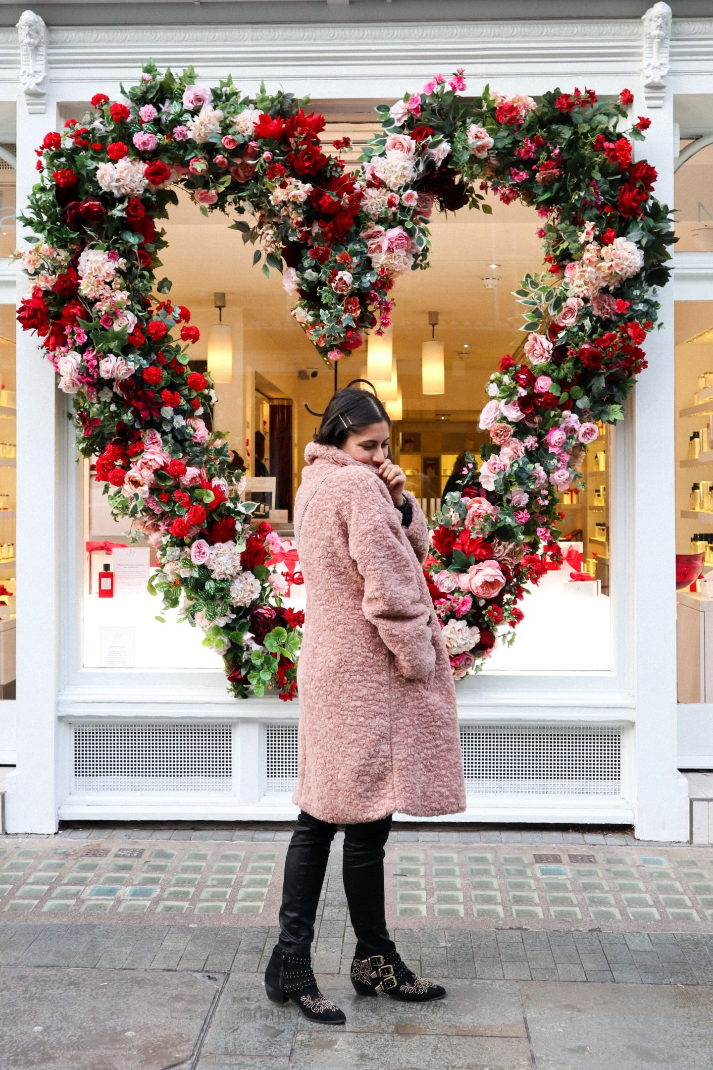 Girl in front of Flower Display in London, wearing pink coat